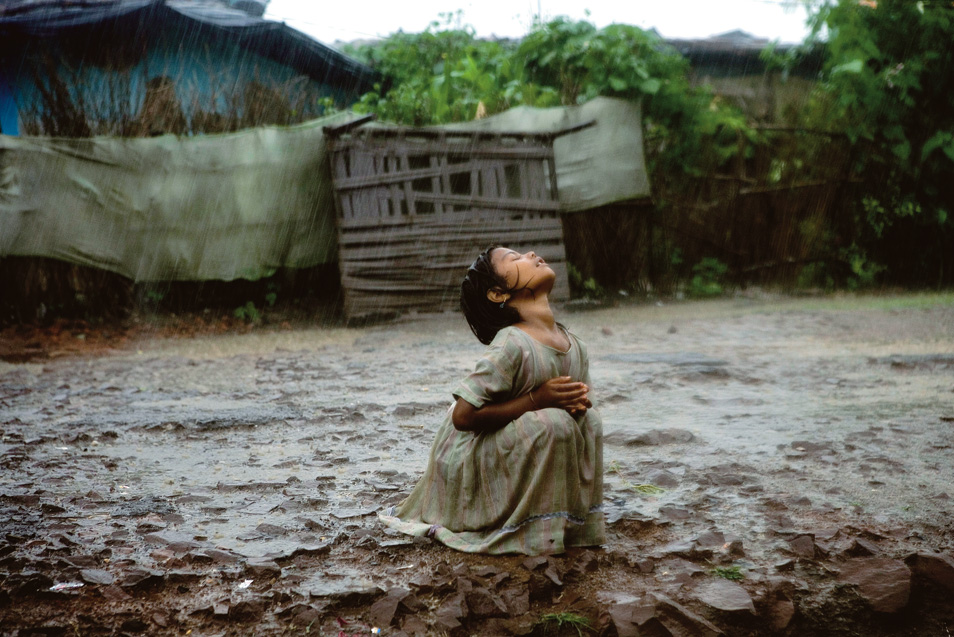 A lone girl is refreshing under the late monsoon rain in the impoverished Oriya Basti Colony in Bhopal. The rain will reach the chemical waste buried under the ground and then poison the drinking water for the over 30.000 urban slum dwellers living nearby.