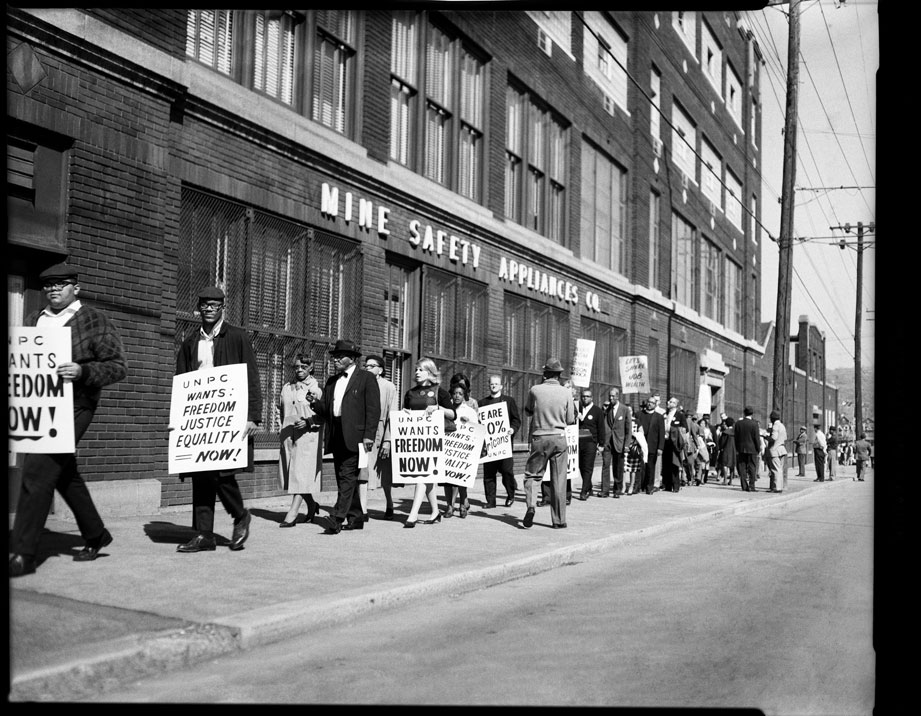 """""""Protesters with UNPC signs outside United Mine Safety Appliance Company, Braddock Avenue, Homewood"""" by Teenie Harris © 2006 Carnegie Museum of Art, Pittsburgh"""
